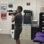 Photo of Ray filming in the AILH Oahu office