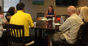 Photo of Kathleen speaking to VI and Blindness group around conference table