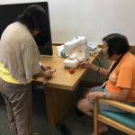 Photo of Elsie getting instructions from Sewing Instructor, Iris