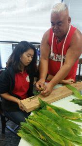 Photo of Tama teaching Krystaleia how to make ti leaf lei