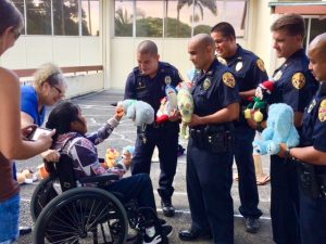 Photo of AILH consumer giving police officers stuffed animals