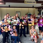 Group photo of police officers, AILH staff and volunteers holding stuffed animals