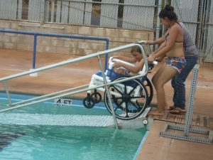 Photo of Felix's mom and sister taking him out of pool