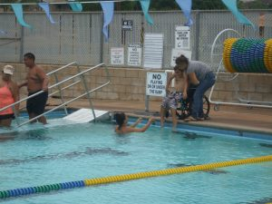 Photo of Felix's mom and sister getting him into pool