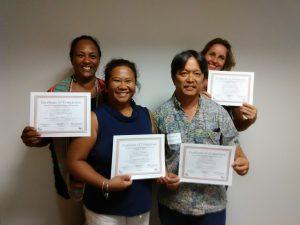 Photo of Julie, Lani, Tom, and Karin holding certificates