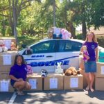 Photo of staff next to police car with boxes of stuffed animals