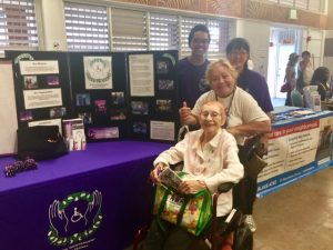 Photo of Ray, Lisa, and 2 visitors to the AILH table