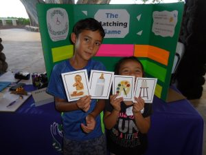 Photo of two keiki holding matching cards