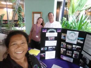 Photo of Lani, Kathleen, and Brian standing by AILH booth