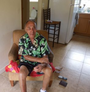 Photo of Avard sitting on chair in his new home