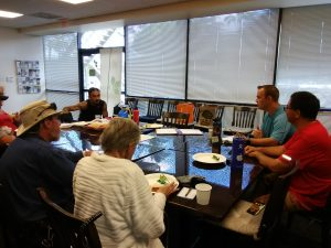 Photo of group sitting around conference table talking