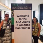 "Photo of Sam and Roxanne standing next to sign that reads ""Welcome tot he ASA Aging in America Conference"""