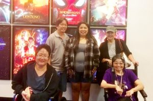 Photo of Hui Malama Po`o members standing in front of movie posters